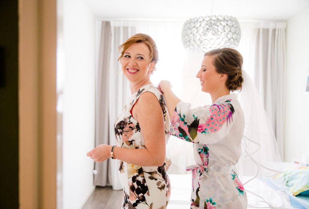 bruid helpt moeder in jurk